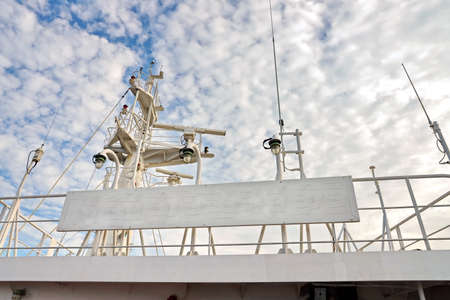 Ship structures, masts, antennas, funnel, ship wheelhouse against the blue sky and clouds. Reklamní fotografie
