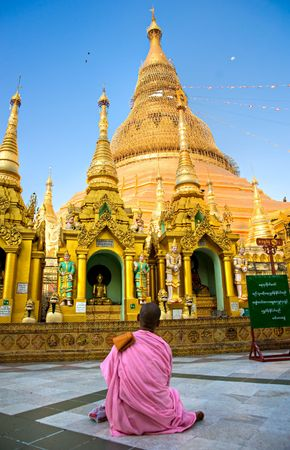 Young Lady monk praying at the Shwedagon Paya, the most sacred buddhist temple in Myanmar,  Yangoon, Myanmar. photo