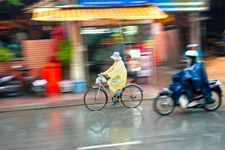 is raining: Motion blur astract of a bike and a motorbike rider in Ho Chi Minh City, Vietnam