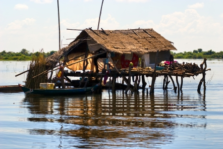 tonle sap: Typical House on the Tonle sap lake, with a small houseboat  Cambodia