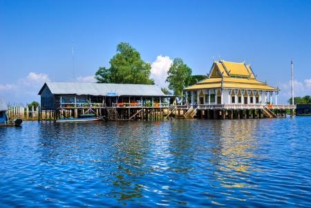sap: Floating House and temple on the Tonle sap lake, with a small houseboat  Cambodia  Stock Photo