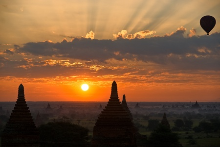 Silhouette of Buddhist Pagodas at sunrise with Hot Air Balloon, Plain of Bagan, Myanmar.  photo