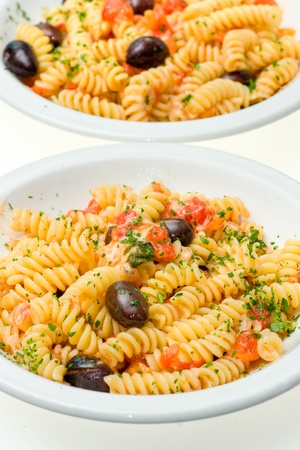 Two dish of IFusilli with cheese, fresh tomatoes and olives. Isolated on white. Stock Photo - 9077213
