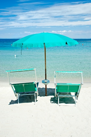 recliner: Two beach chairs with green umbrella.