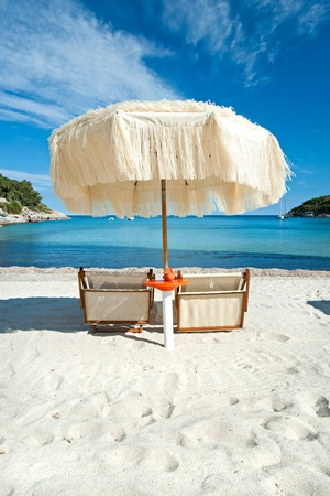 Two beach chairs with umbrella.