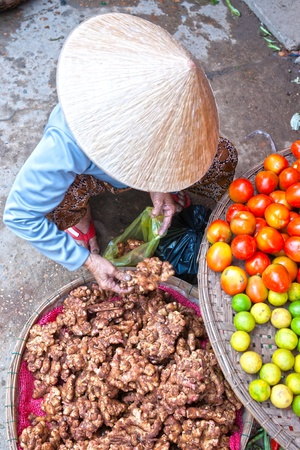 Vietnamese woman selling ginger in a market, Ho chi minh city, Vietnam.