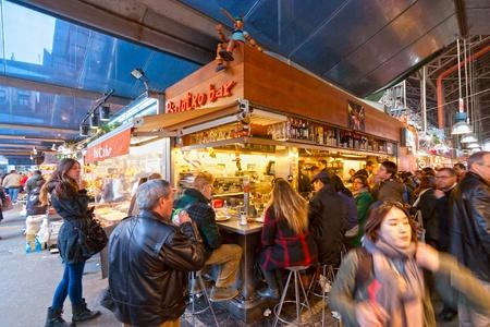 sugarcoat: BARCELONA, SPAIN - DECEMBER 20: Tourists shop in famous La Boqueria market on December 20, 2011 in Barcelona, Spain. One of the oldest markets in Europe that still exist. Established 1217.