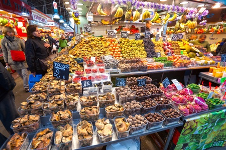 BARCELONA, SPAIN - DECEMBER 20: Tourists shop in famous La Boqueria market on December 20, 2011 in Barcelona, Spain. One of the oldest markets in Europe that still exist. Established 1217. Stock Photo - 12877749