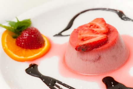 Italian dessert panna cotta on white plate decorated with coconut milk and peach. photo