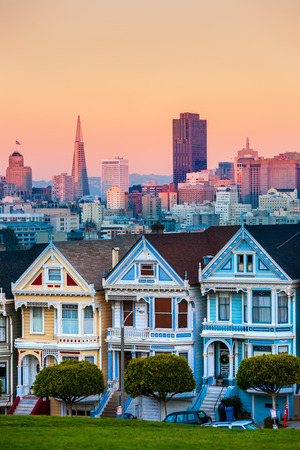 The Painted Ladies of San Francisco, California sit glowing amid the backdrop of a sunset and skyscrapers. Фото со стока