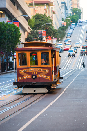 SAN FRANCISCO, USA - DECEMBER 16: Passengers enjoy a ride in a cable car on Dec 16, 2013 in San Francisco. It is the oldest mechanical public transport in San Francisco which is in service since 1873.
