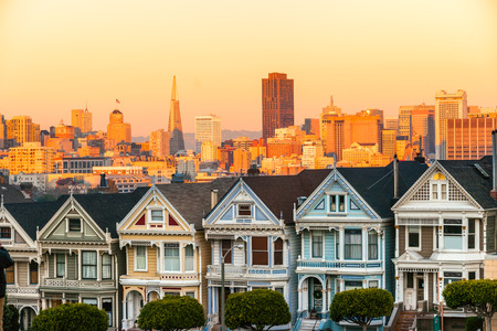 The Painted Ladies of San Francisco, California sit glowing amid the backdrop of a sunset and skyscrapers. photo