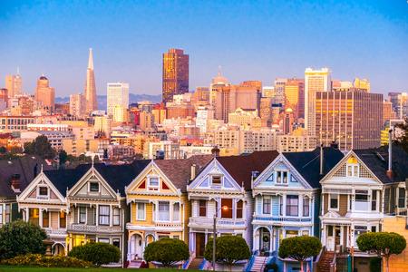 샌프란시스코, 캘리포니아의 그린 여성은 일몰과 고층 빌딩의 배경 속에서 빛나는 앉아.