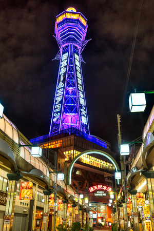 advertises: OSAKA - NOVEMBER 24: Tsutenkaku Tower in Shinsekai (new world) district at night on November 24, 2014, in Osaka. It is a tower and well-known landmark of Osaka, Japan and advertises Hitachi, located in the Shinsekai district of Naniwa-ku, Osaka.