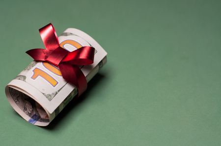 christmas bonus: Rolled U.S. one hundred dollar bill, tied with red ribbon and a bow. The bow color suggests a Christmas gift, bonus, birthday present, or special occasion. Isolated on a green background.