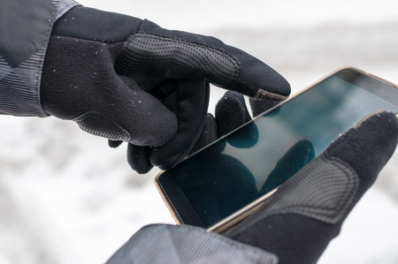 Closeup of man using smartphone in winter with winter gloves for touch screens Фото со стока