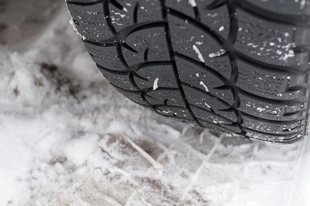 winter tyre: Closeup of Winter tyre on the road covered with snow