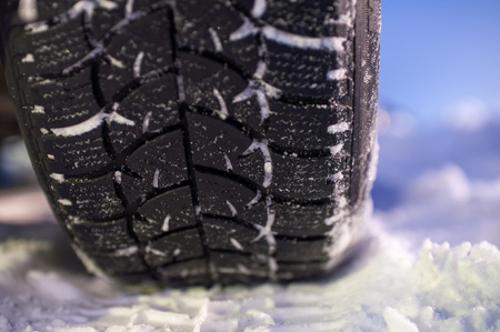 winter tyre: Closeup of winter tyre on the road, selective focus, shalow depth of field Stock Photo