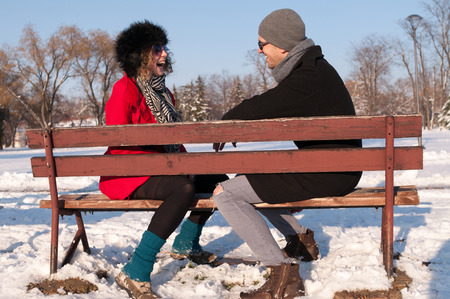 Young couple sitting on bench in park in winter and smiling Фото со стока