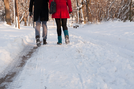 Couple holding each others hands going through the park in the winter, low section