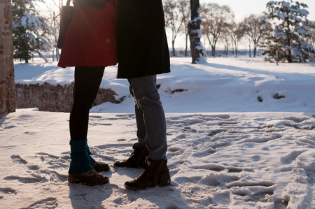 Romantic couple standing and embracing on snow  outdoors in winter, low section