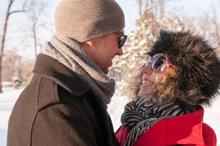Couple Laughing In The Park Together in winter on snow Фото со стока