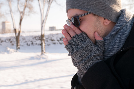 Man sneezing outdoors on the snow in winter