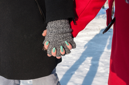 Young couple holding hands standing outdoors in winter, closeup