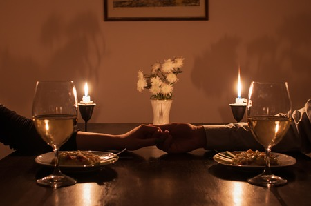 romantic evening with wine: Loving couple holding hands during romantic dinner