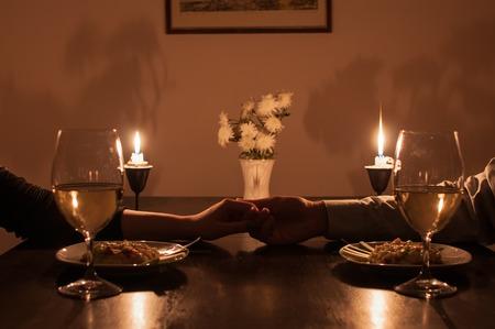 dattes: Loving couple se tenant la main pendant le dîner romantique