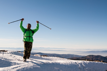 conquer: Hiker happy to conquer the mountain peak outstretching his arms