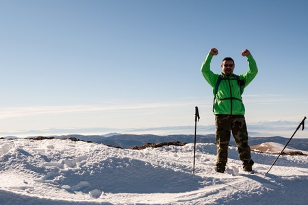 Hiker happy to conquer the mountain peak outstretching his arms