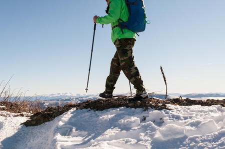 Mid section of a male backpacker walking on mountain peak.