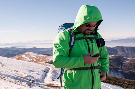 40 44 years: Hiker checking his smartphone on the top of the mountain