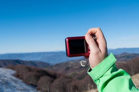 Hiking man taking photo with digital camera on mountain peak