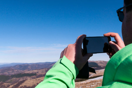 Young man hiker photographing the landscape using a mobile phone
