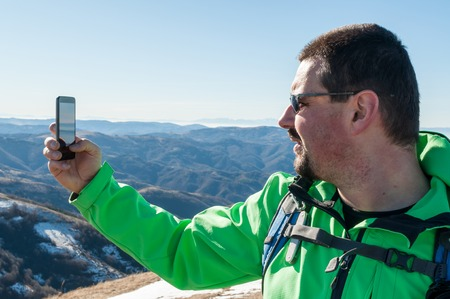 Young backpacking man taking a photo of himself in mountains with smart phone Фото со стока