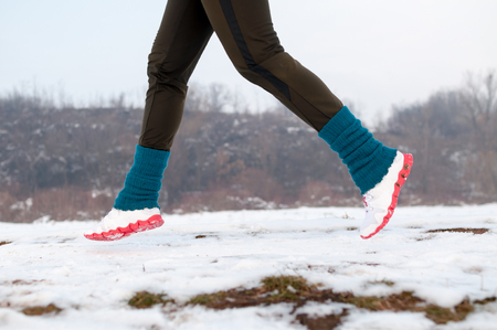 Low section of female runner running on snow