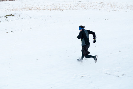 Healthy young man jogging outside on snow, athlete running on winter day