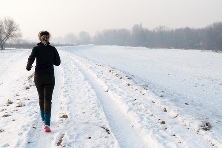 Healthy young woman jogging outside on snow, athlete running on beautiful winter day