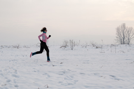 Healthy young woman jogging outside on snow, athlete running on winter day