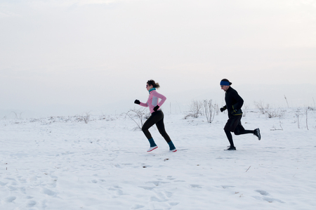 Healthy young couple jogging outside on snow, athlete running on winter day