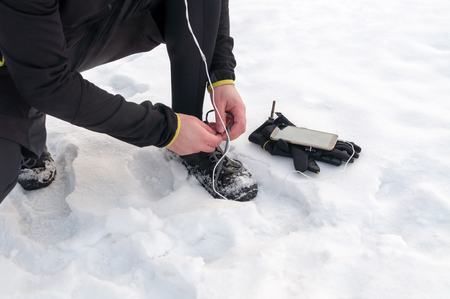 Young sport man tying running shoes during winter training outside in cold snow weather 版權商用圖片