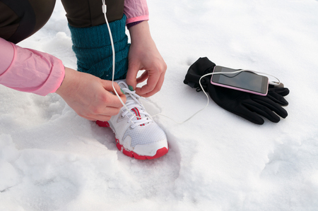 Young sport woman tying running shoes during winter training outside in cold snow weather