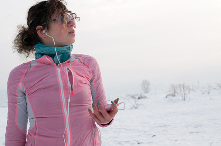 Girl runner enjoying outside on snow after running on winter day and listen music in earphones from smartphone.