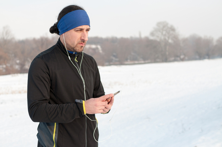 Male runner enjoying outside on snow after running on winter day and listen music in earphones from smartphone.