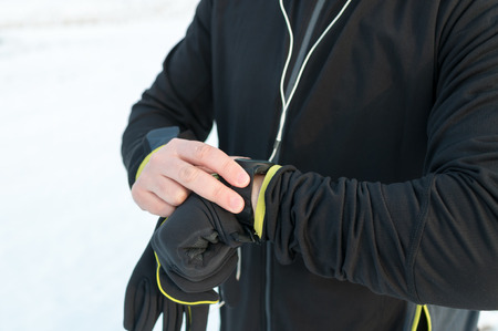 Runner using heart rate monitor, smartwatch checking performance or GPS. Man athlete looking at stopwatch. Technology for tracking activity. Outside, snow, winter