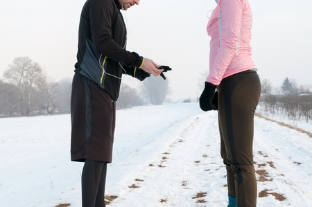 Man and woman warming up and preparing before running outside on snow on winter day