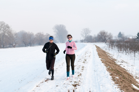 Healthy young couple jogging outside on snow, athlete running on beautiful winter day Фото со стока