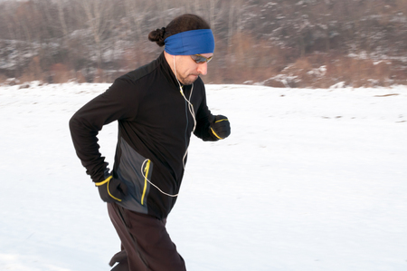 Male athlete running outdoor on cold winter day. Running, jogging, sport, fitness, active lifestyle concept, cold weather training. Motion blur.